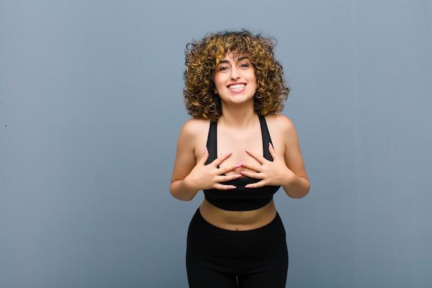 幸せ、驚いて、誇りに思って、興奮して、灰色の壁に自己を指している若いスポーツ女性