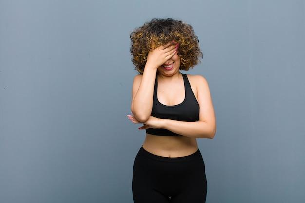 灰色の壁に手で顔を覆っている、ストレス、恥ずかしさ、または動揺、頭痛で探している若いスポーツ女性