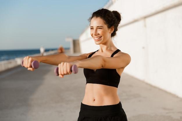 若いスポーツの女性は、ビーチで屋外のダンベルで運動をします。