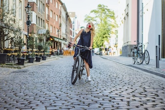 Young sports woman on a bicycle in a European city. Sports in urban environments.