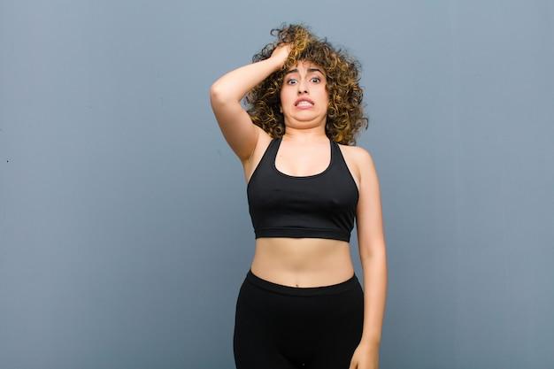 忘れられた締め切りをて、ストレスを感じ、混乱を隠さなければならない若いスポーツ女性