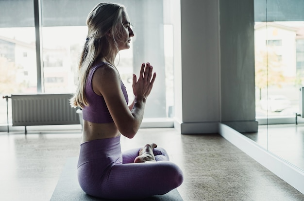 Young sports woman practicing yoga, meditation in lotus position with namaste, workout, yoga studio