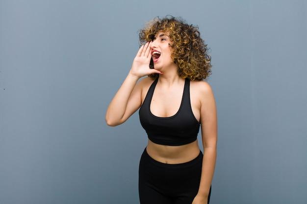 若いスポーツ女性プロフィールビュー、幸せそうに見えて興奮して、叫び、灰色の壁に対して側のスペースをコピーするように呼び出し