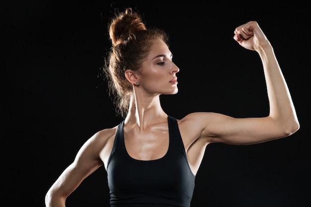 La giovane donna di sport che mostra il suo bicipite