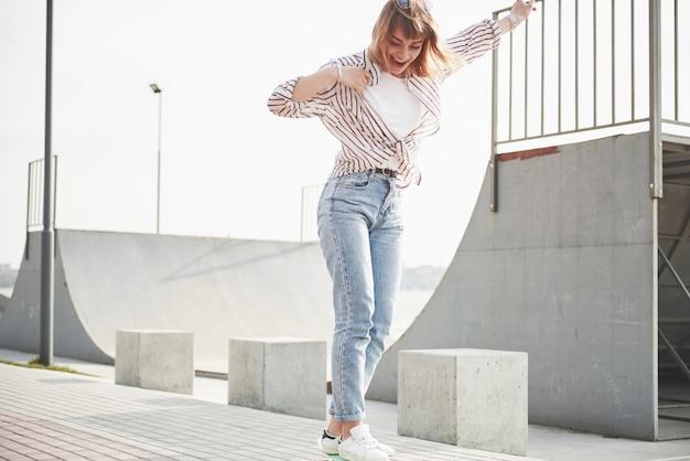 Una giovane donna sportiva che cavalca in un parco su uno skateboard.