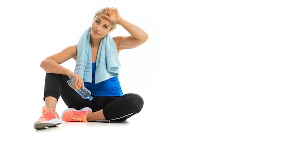 A young sports woman with blonde hair in a black sports axe, black leggings and bright sneakers with a towel around her neck and a bottle of water tired after training.