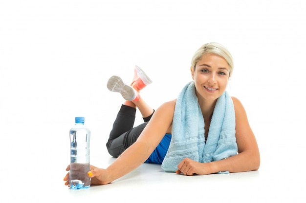 Young sports woman with blonde hair in a black sports top, black leggings and bright sneakers with a towel around her neck and a bottle of water lies