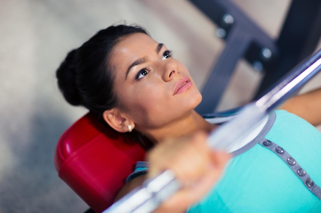Young sports woman workout with barbell on the bench in fitness gym