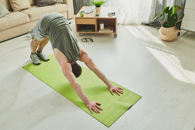 Young sportsman in activewear bending forwards while standing on the floor with his feet and hands on mat during workout in living-room