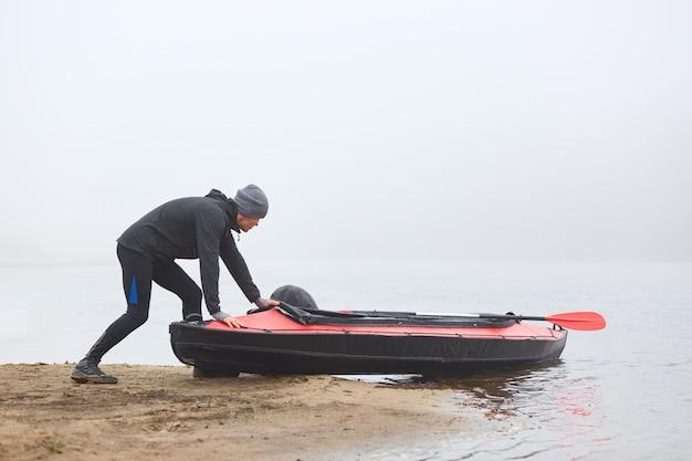 Молодой спортсмен готовится к гребле на каноэ, толкая лодку в воду
