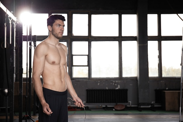 ジムで縄跳びのトレーニングをしている若いスポーツマン。