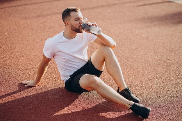 スタジアムで水を飲む若いスポーツマン