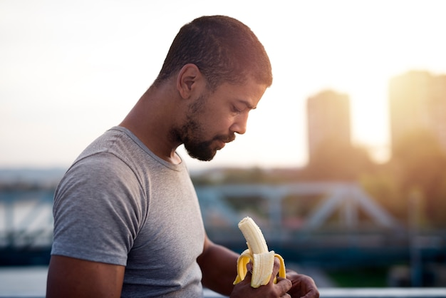 Young sportsman eating banana after training