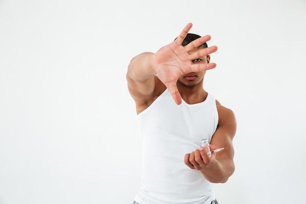 Молодой спортсмен держит шприц