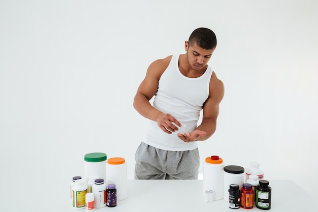 Young sportsman holding vitamins and sport pills.