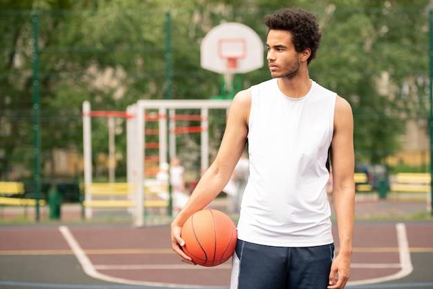コートでバスケットボールのトレーニングの合間に休憩しながら脇を見てアクティブウェアの若いスポーツマン