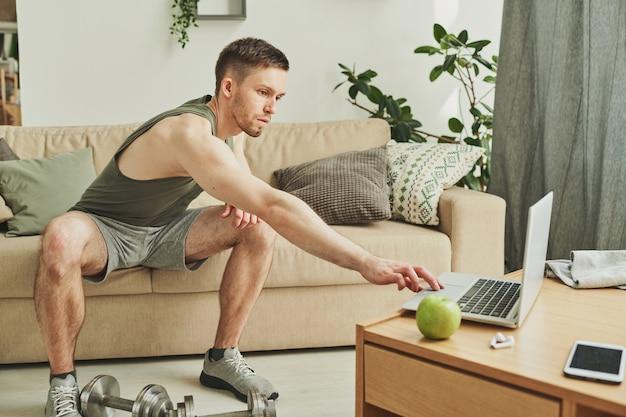 Молодой спортсмен в спортивной одежде сидит на диване, протягивая руку к ноутбуку, чтобы нажать кнопку пуска и смотреть онлайн-видео тренировки
