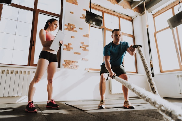 Young sportsman is exercising in gym with trainer