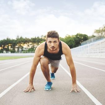若いスポーツマンは、朝屋外で実行する準備ができています。