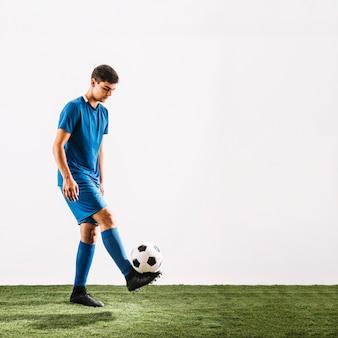 Молодой спортсмен, жонглирующий мяч