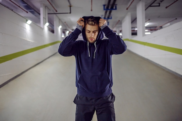Молодой спортсмен надевает толстовку на голову, стоя в подземном гараже.