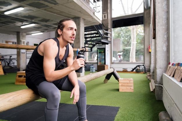 체육관에서 그의 운동에서 휴식하는 젊은 스포츠맨