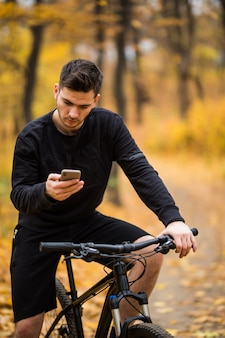 Young sportsman riding bicycle holding phone, sunny autumn park