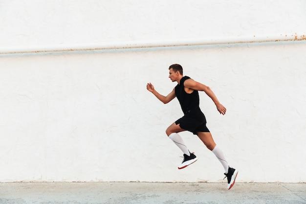 屋外で走っている若いスポーツマン