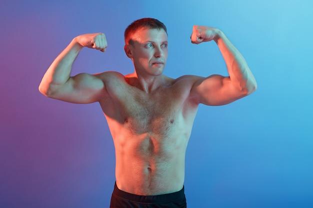 Молодой спортсмен показывает мышцы и задумчиво смотрит в сторону