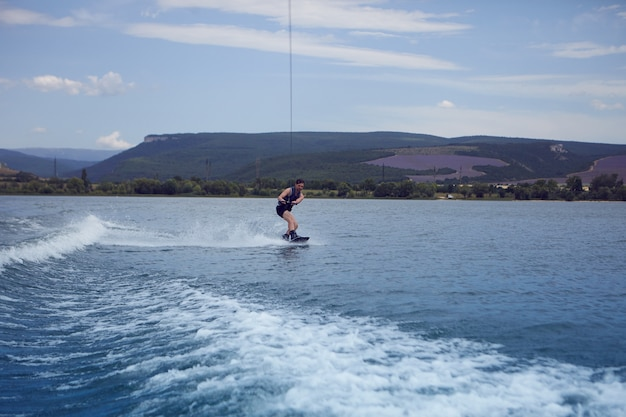Young sportsman surfing across lake. surfer wearing wet swimsuit training in wake park, wakeboarding on river, pulled by motor boat, clinging to cable. wakesurfing, waterskiing, sports and recreation