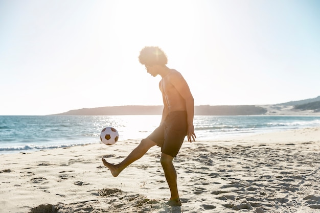 Young sportsman tossing up ball on seacoast