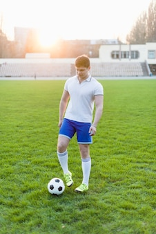 Young sportsman touching ball with boot