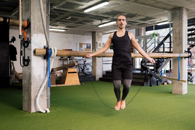 Young sportsman training by jumping rope at gym