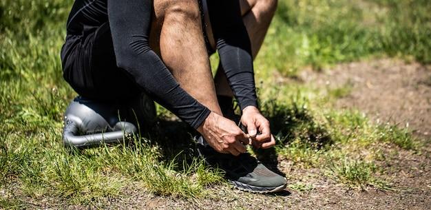 スポーツシューズの靴ひもを結ぶ若いスポーツマン
