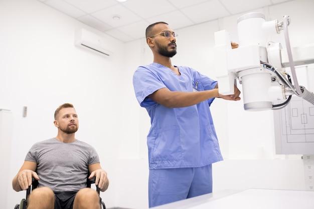 새로운 의료 장비를 테스트하는 그의 의사를 보면서 휠체어에 앉아 아픈 다리를 가진 젊은 운동가