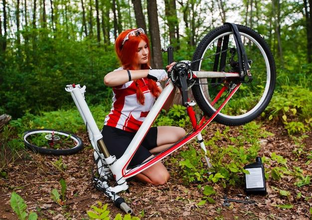 Молодая спортсменка велосипедист ремонтирует свой mtb велосипед в лесу