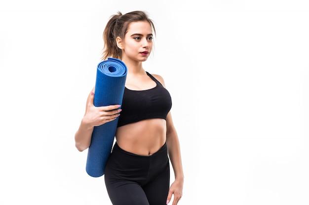 Young sportswoman in black sportswear practicing yoga on a mat.