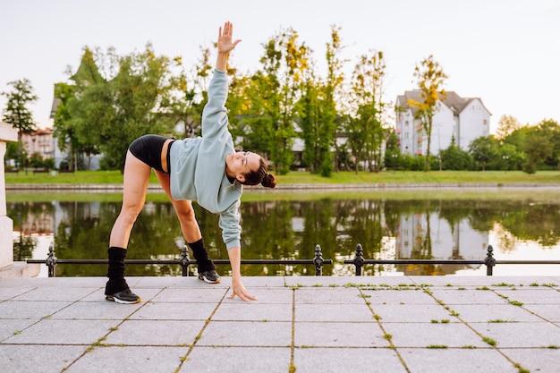 젊은 운동가는 호수 근처 공원에서 달리기 전에 복잡한 스트레칭 운동을 한다