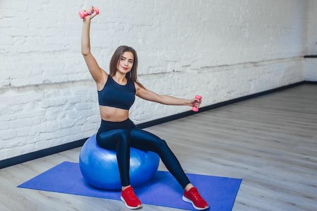 Молодая спортсменка делает упражнения с мячом на коврике дома и с розовыми гантелями.