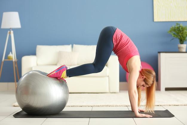 Молодая спортсменка делает упражнения с мячом на коврике дома