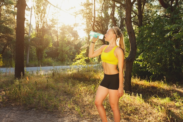 Young sportswoman drinking water after run