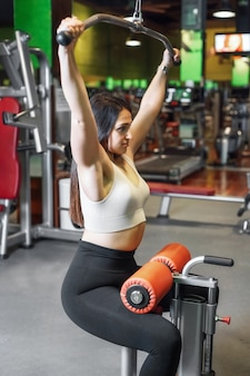 Young sportswoman exercising on lat machine in gym.