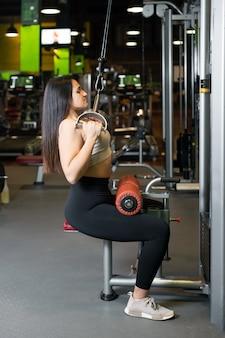 체육관에서 위도 기계에서 운동하는 젊은 sportswoman.