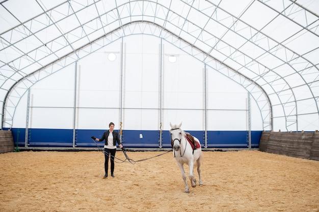 トレーニング中に砂浜の円形競技場を移動する白い競走馬の添え金を保持している若いスポーツ選手