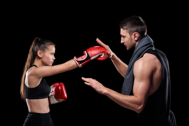 Молодая спортсменка в спортивной одежде и боксерских перчатках тренируется с тренером, консультируя ее о правилах боя