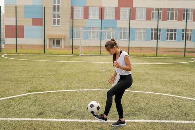 Молодая спортсменка в спортивной одежде, пиная футбольный мяч во время тренировки на поле или игровой площадке перед матчем