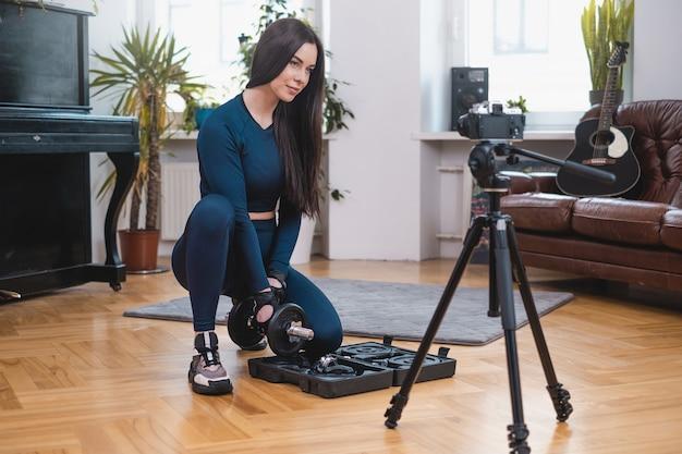 紺色の服を着た若いスポーツウーマンがカメラでポーズをとり、モダンなアパートでスポーツ用品を準備します。