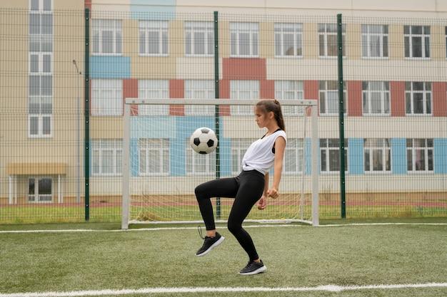Молодая спортсменка в леггинсах, кроссовках и футболке тренируется играть в футбол, отбивая мяч на открытой площадке