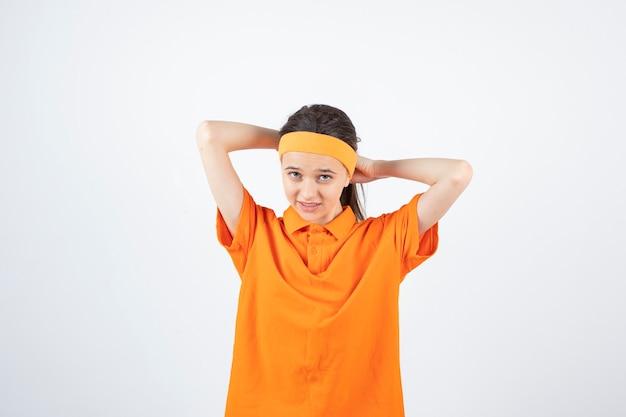 オレンジ色の衣装を着た若いスポーツウーマンが立ってヘッドバンドを取っています。