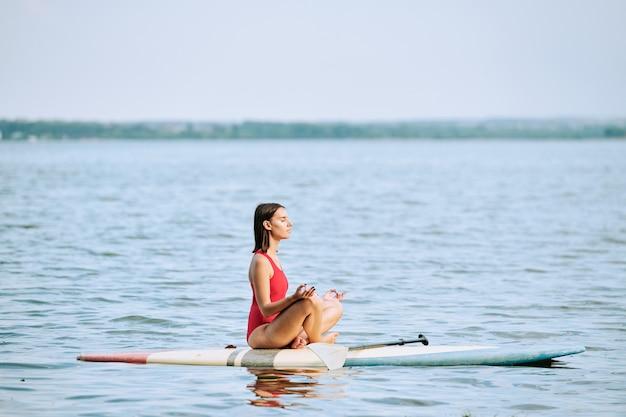요가를 연습하는 빨간 수영복을 입은 젊은 운동가 프리미엄 사진